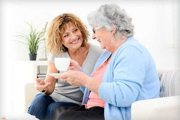 Caregiver and female client having coffee