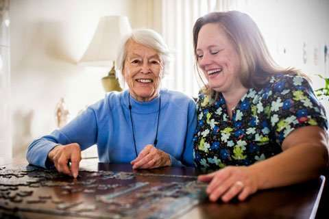 Caregiver and client doing a jigsaw puzzle