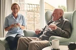 senior man and caregiver laughing